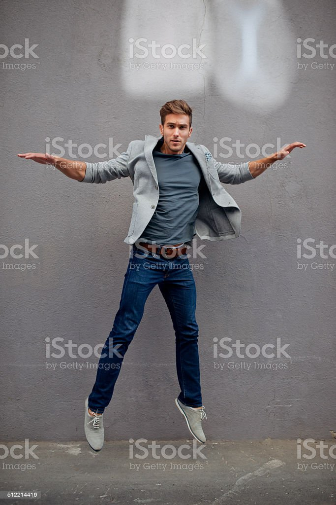 Trendy elegant guy jumping stock photo