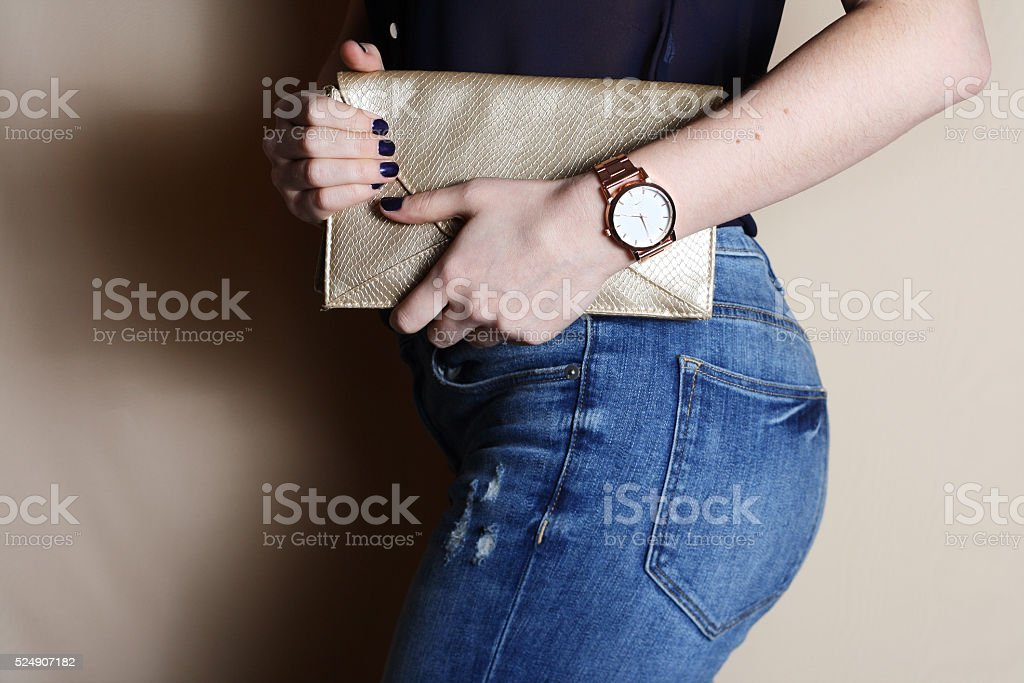 trendy girl with gold clutch and watch Beauty, fashion concept. stock photo