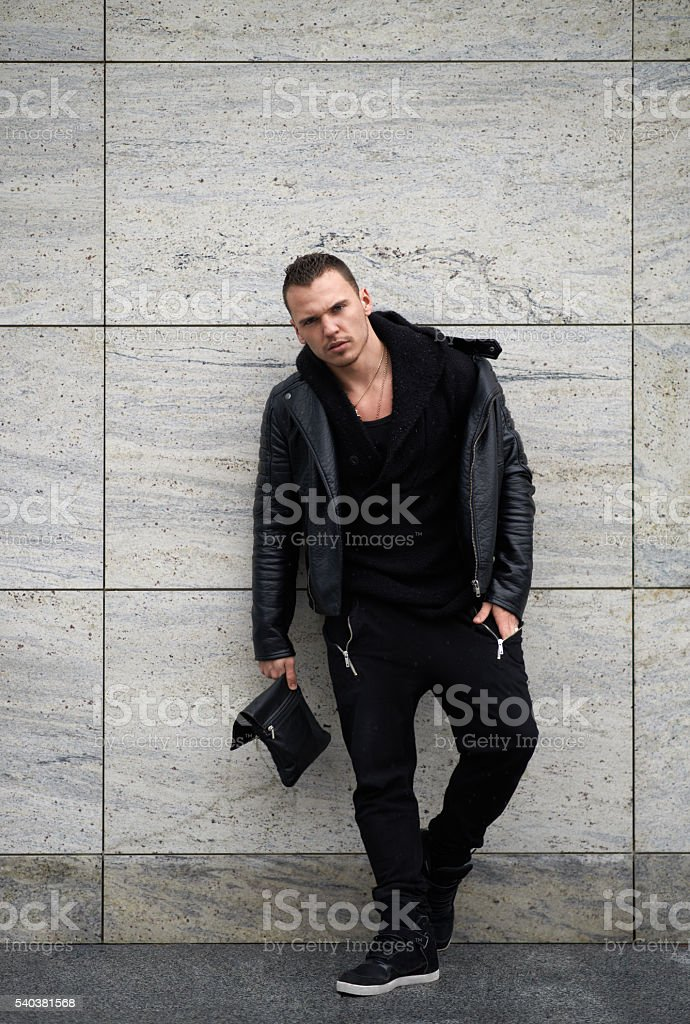 trendy guy standing near  wall stock photo