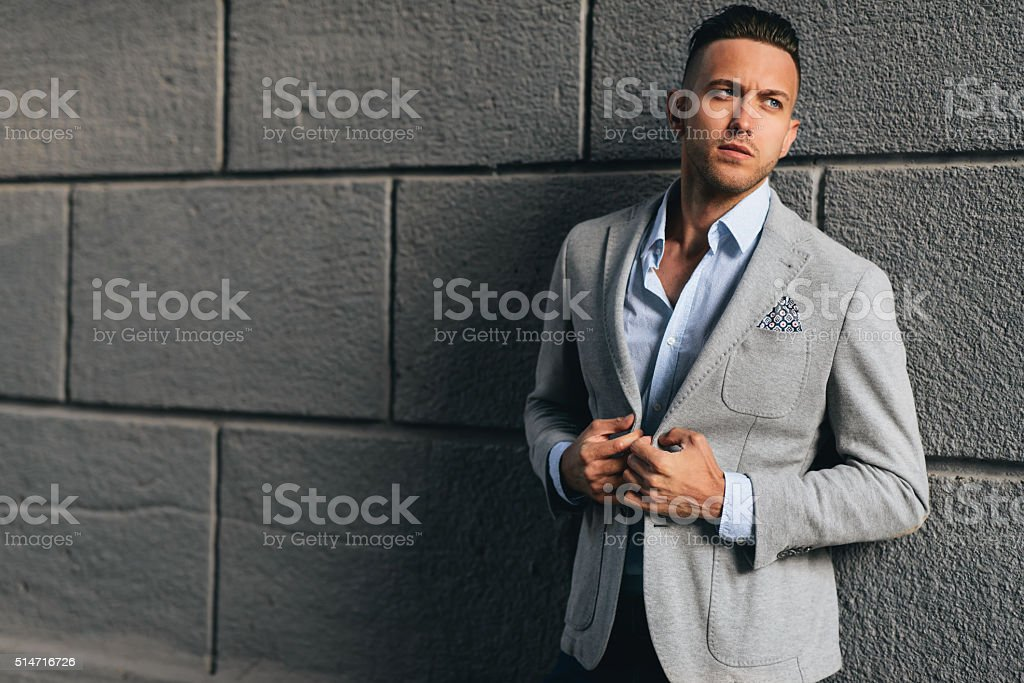 Trendy handsome man standing near the wal stock photo