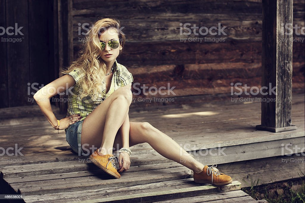 Trendy Hipster Girl Sitting on the Wooden Porch stock photo