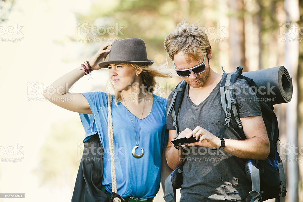 Trendy Hipsters Hiking and Using a Smart Phone royalty-free stock photo