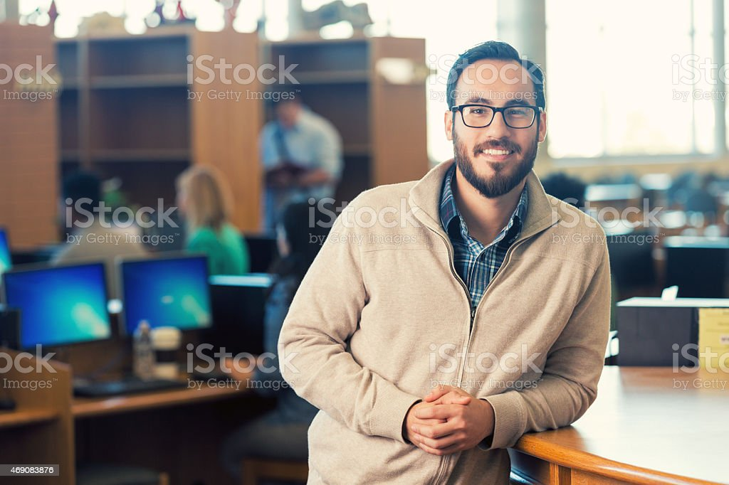 Trendy Hispanic hipster man smiling in college library stock photo