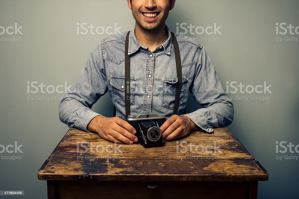 Trendy man with vintage camera at old desk royalty-free stock photo