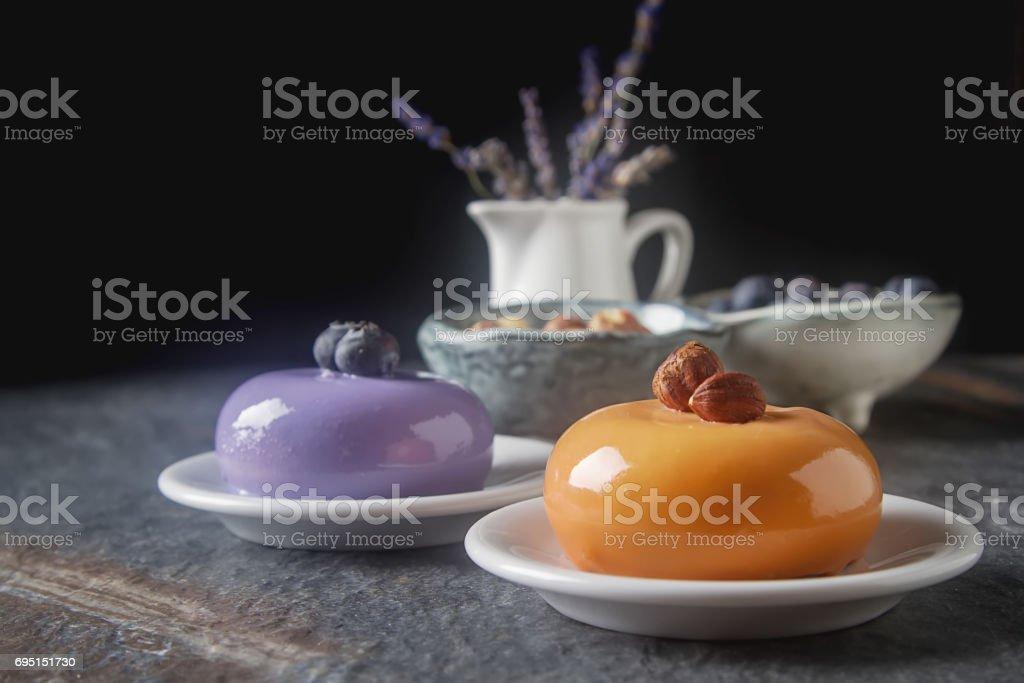Trendy mousse cake with mirror glaze decorated. Dark background. stock photo