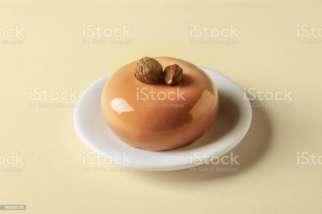 Trendy mousse cake with mirror glaze decorated. Yellow background. stock photo