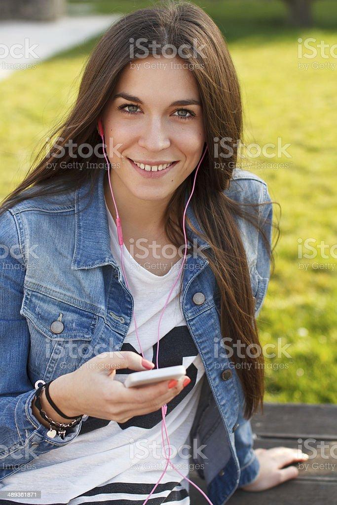 Trendy teenager listening music on smartphone teeth smile royalty-free stock photo