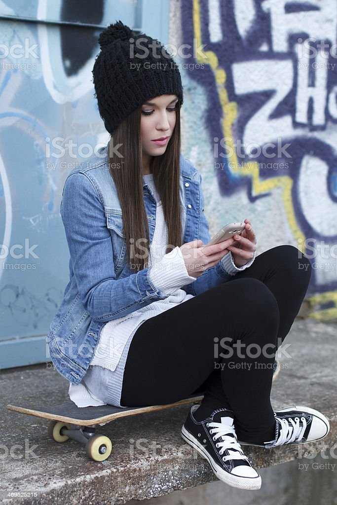 Trendy teenager with smartphone and skateboard royalty-free stock photo