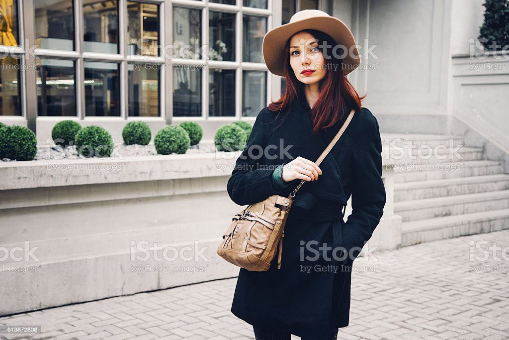 Trendy woman wearing winter coat and hat on the street stock photo
