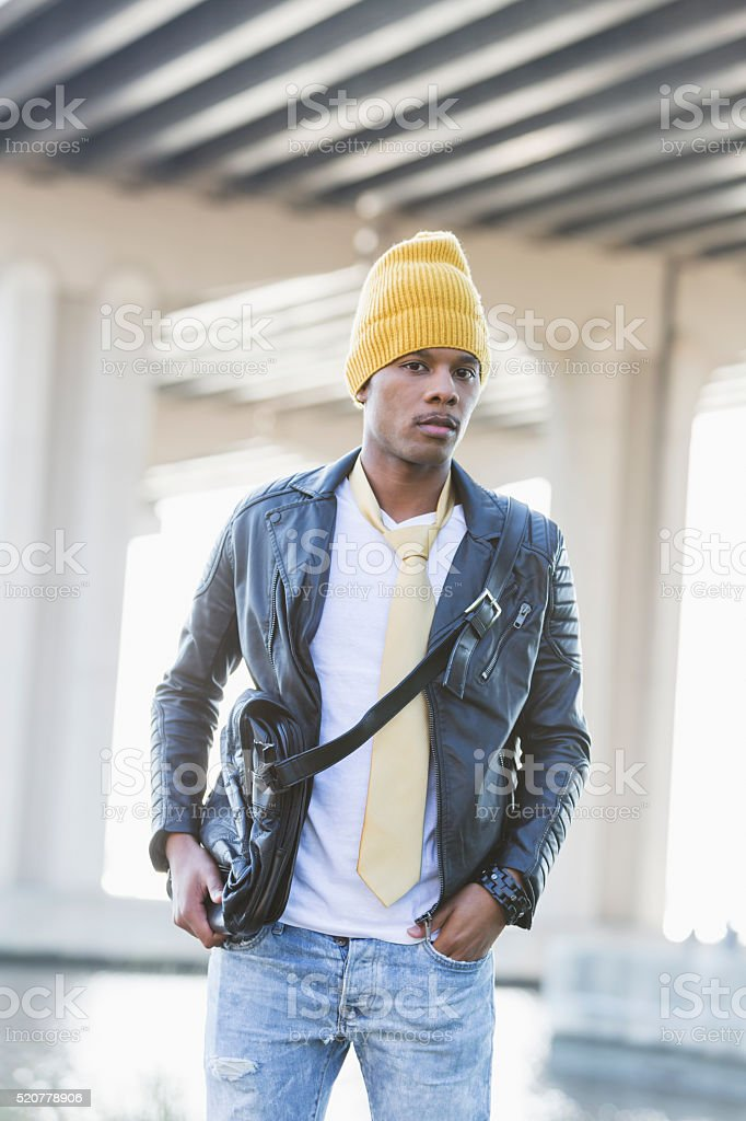 Trendy young black man outdoors wearing yellow beanie stock photo