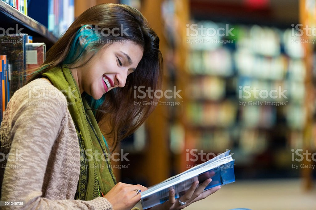 Trendy young college student reading in modern library stock photo