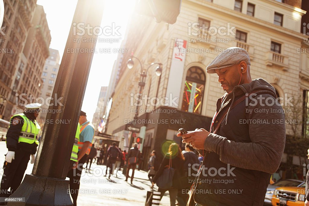 NYC Trendy young man waits to cross 34th Street royalty-free stock photo