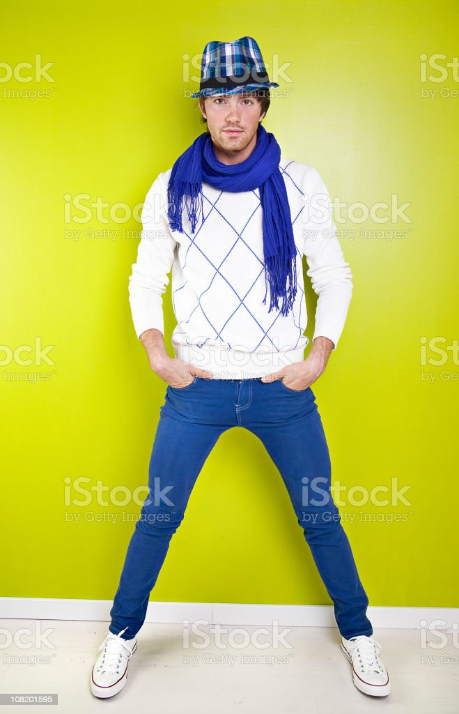 Trendy Young Man Wearing Jeans and Scarf Against Green Wall stock photo
