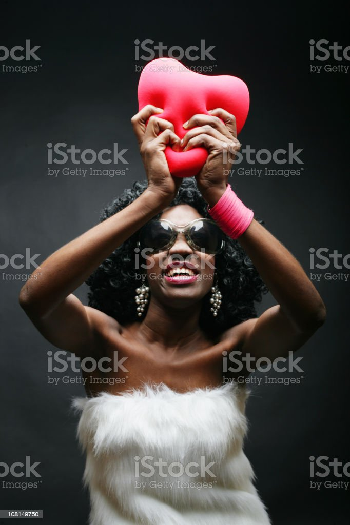 Trendy Young Woman Holding Heart Pillow Up royalty-free stock photo