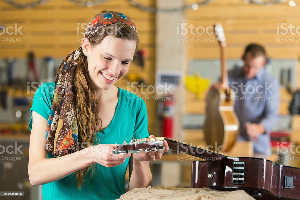 Trendy young woman repairs acoustic guitar stock photo