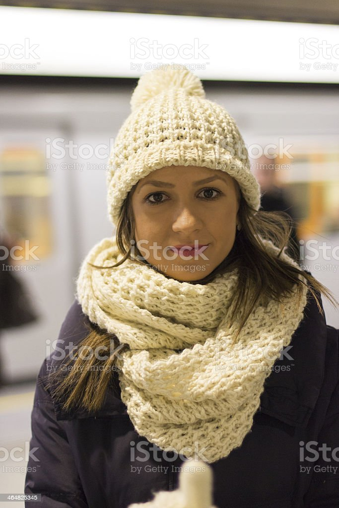 Trendy Young Woman Standing on Subway Station Platform stock photo