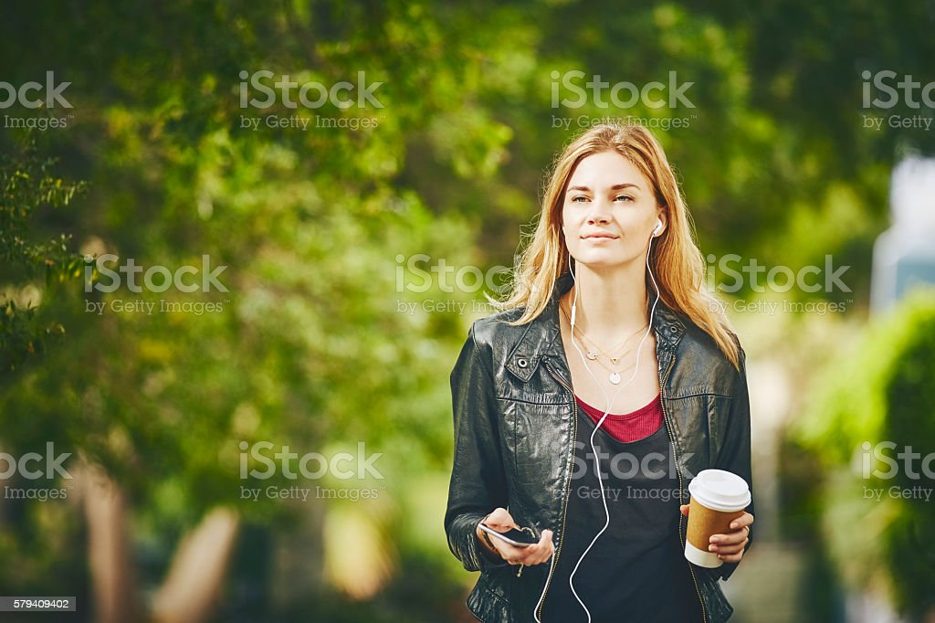 Trendy young woman to listening music while walking stock photo