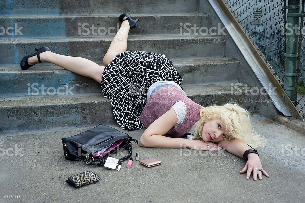 Trendy young woman with a handbag falling down steps  stock photo
