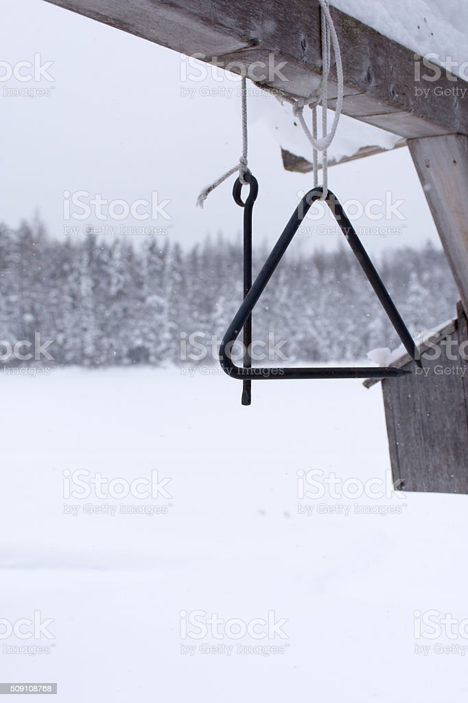 triangle dinner bell hanging from beam in winter stock photo