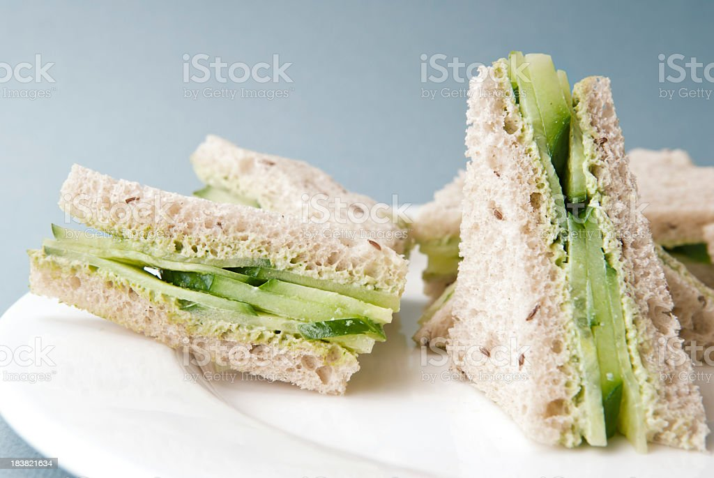 Triangles of cucumber sandwich on a white plate stock photo