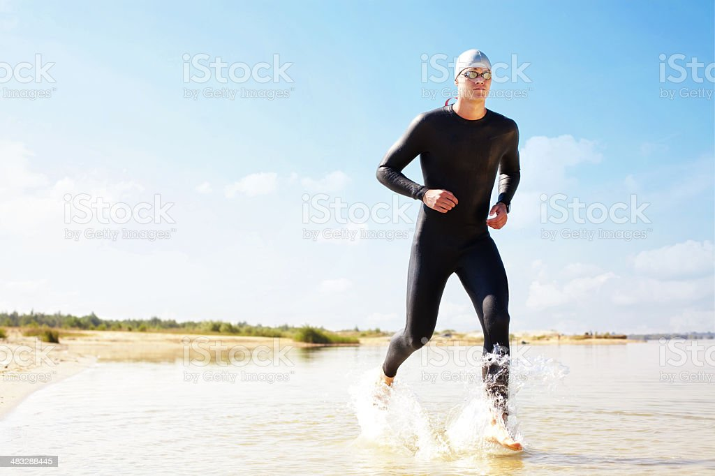 Triathlete running in to the water stock photo