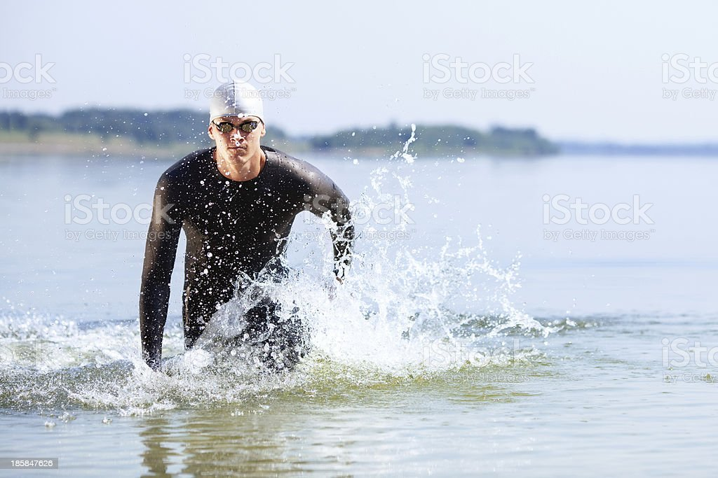 A triathlete running out of a body of water stock photo