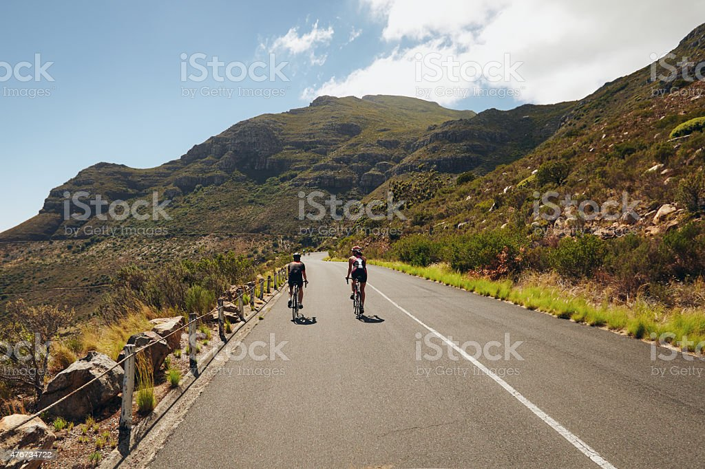 Triathletes practicing cycling on open country road stock photo