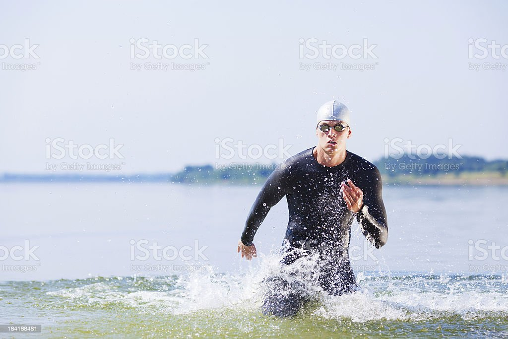 Triathlon athlete running in motion out of the water stock photo