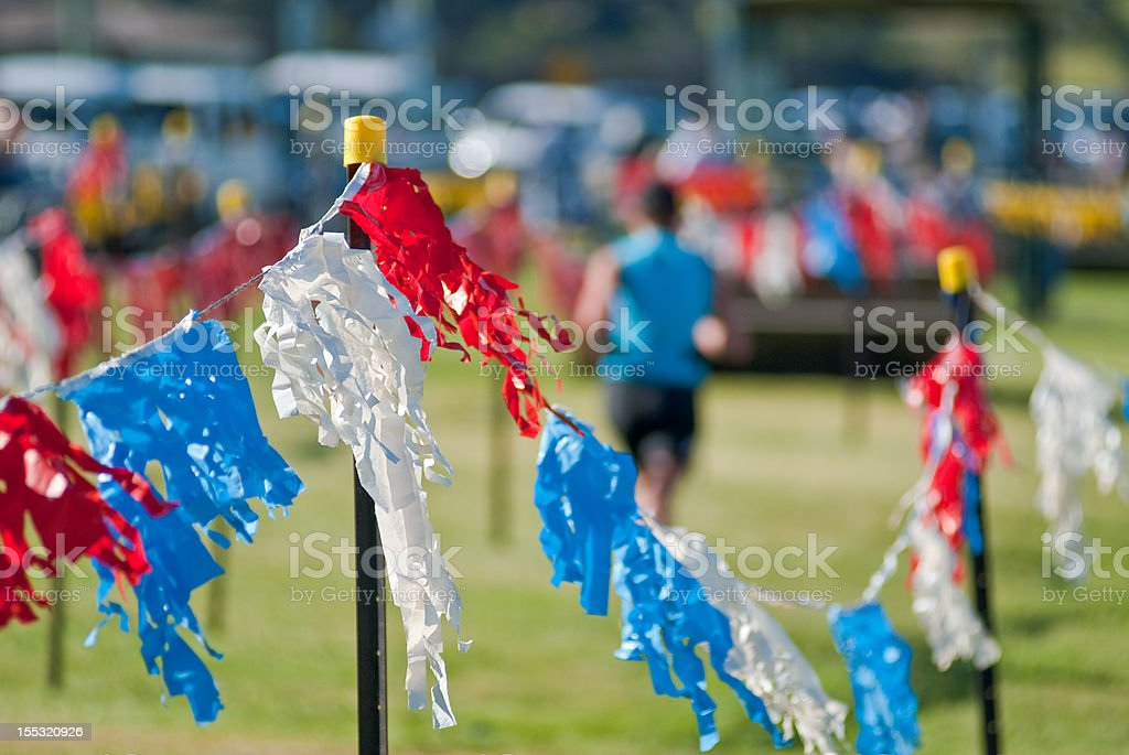 Triathlon finish line with plastic flags and athlete stock photo