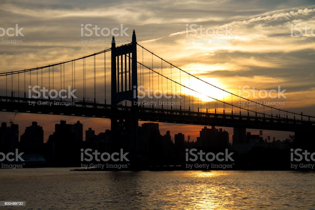 Triborough bridge and city with sunset in silhouette, New York stock photo