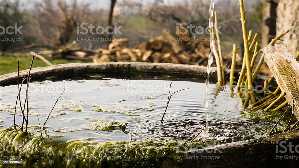 Trickle of water falls into a old round tub. stock photo