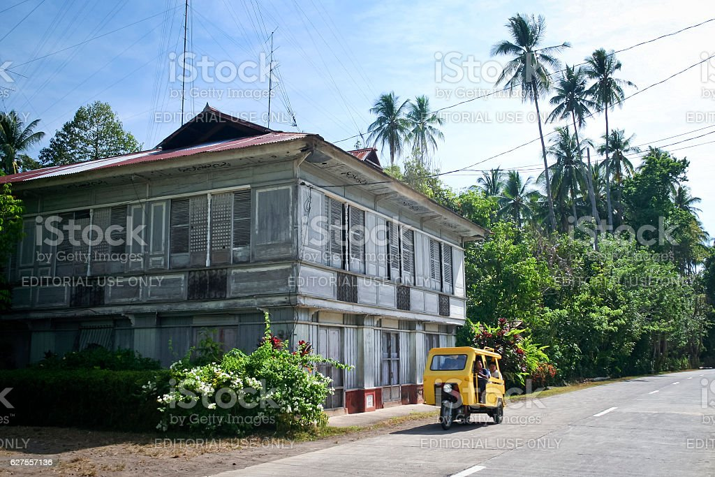 Tricycle Passing Traditional Filipno House on Camiguin Island, Mindanao stock photo