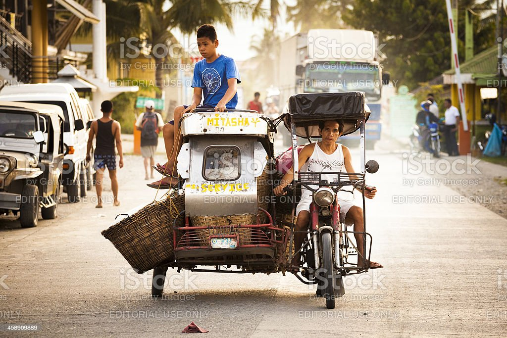 Tricycle with a boy sitting on the roof, Roxas, Philippines stock photo