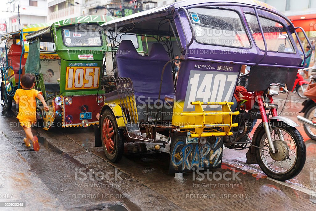 tricycles on dumaguete sidewalk stock photo