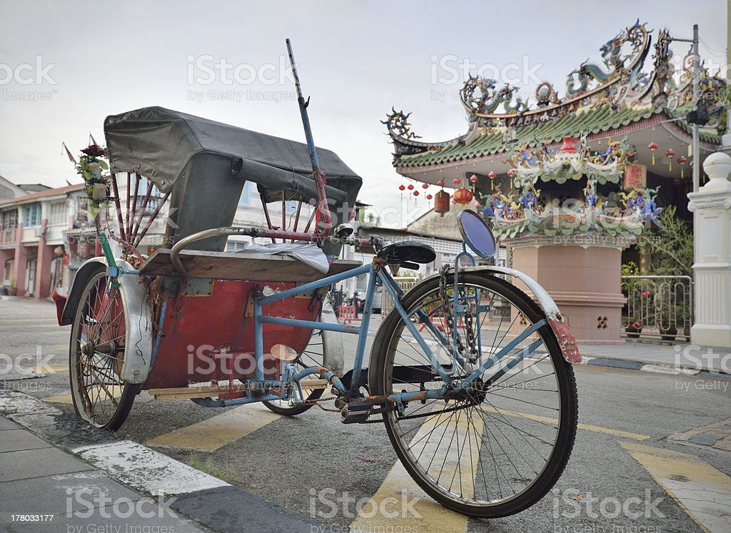 Tricyle and temple in Penang street stock photo