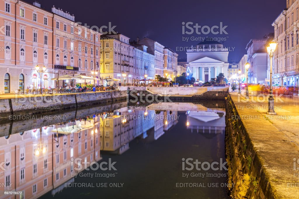 Trieste, Italy: Night view of the main landmark in the city - Grand Canal, historical buildings mirror reflected in the water. Popular tourist destination in Northern Italy stock photo
