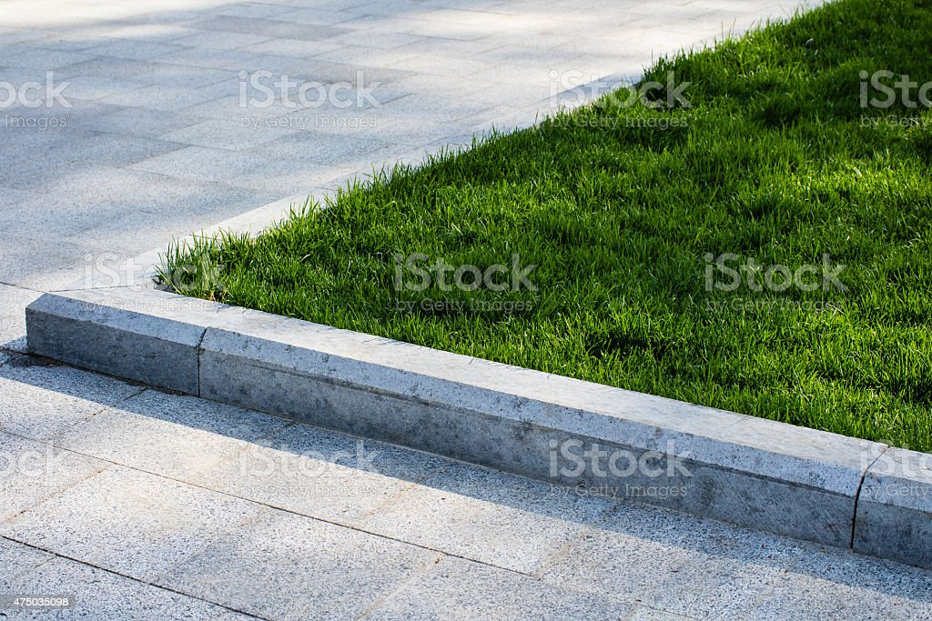 Trim the lawn in the park on the sidewalk stock photo