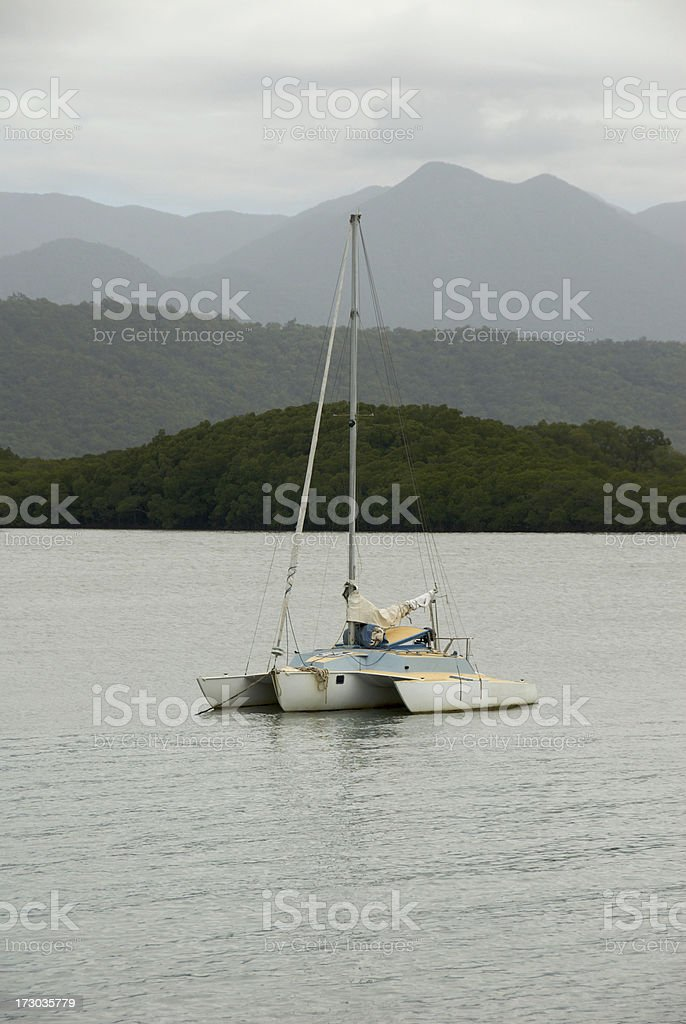 Trimaran at anchor in tropical harbour stock photo