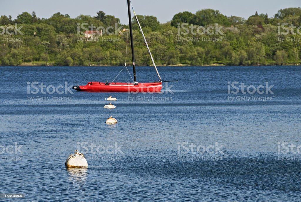 Trimaran moored to buoy in lake stock photo