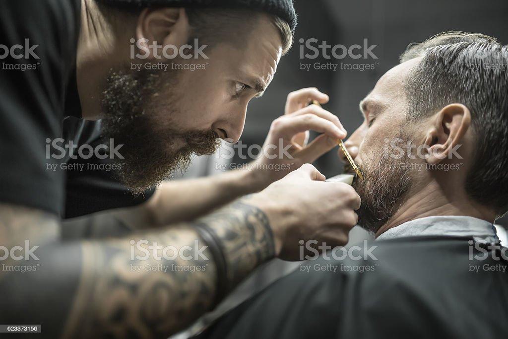 Trimming beard in barbershop stock photo