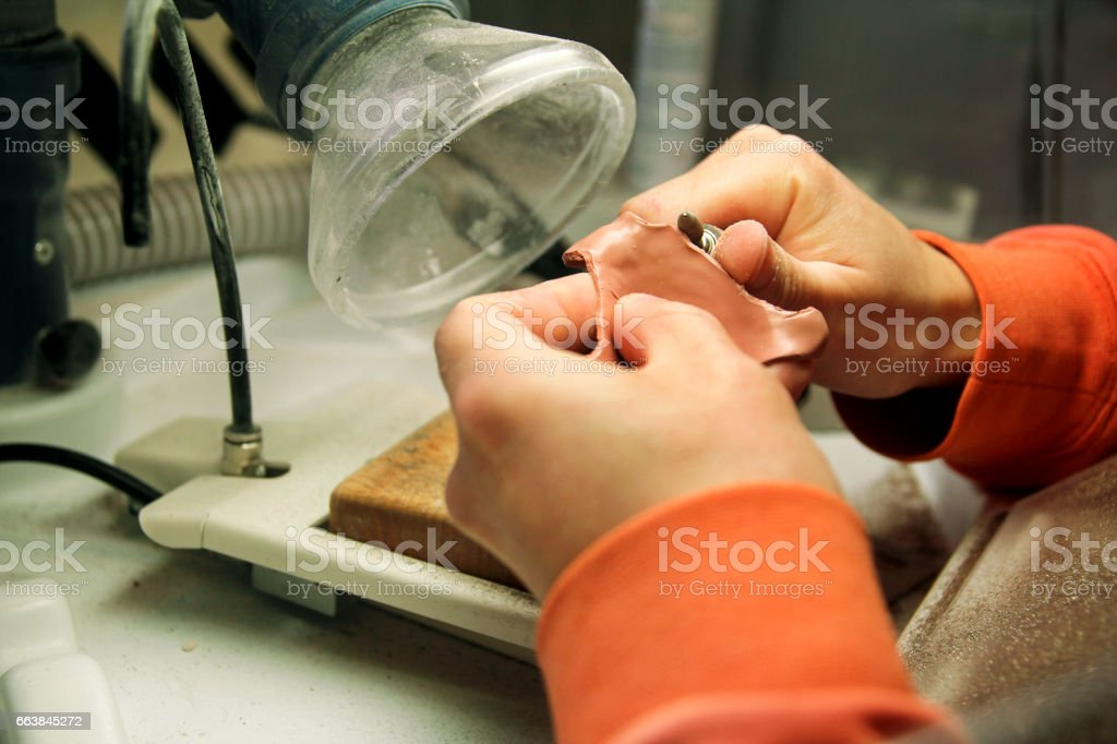 Trimming with micro motor Shellac base plates. Dentures. Dental prosthesis, dentures, prosthetics work. Dental technician in process of making dentures. Trimming with micro motor Shellac base plates. stock photo