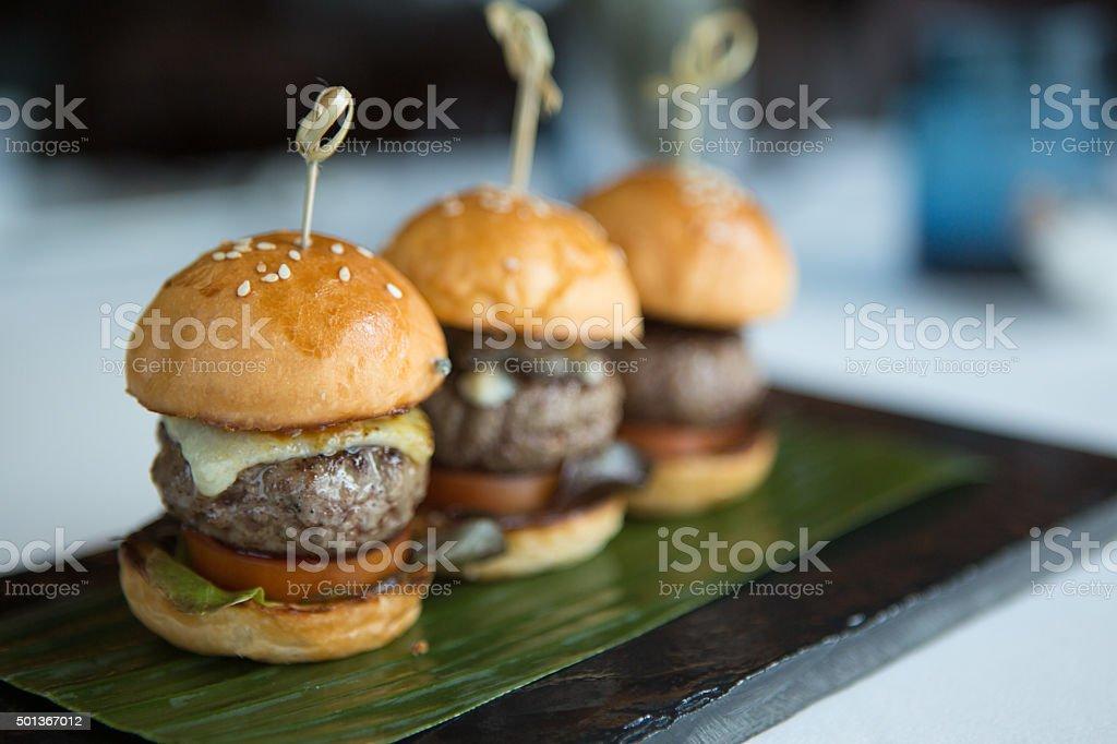 Trio of mini hamburgers served on a banana leave. stock photo