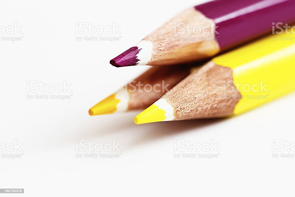 Trio of purple, yellow and gold pencil crayons royalty-free stock photo