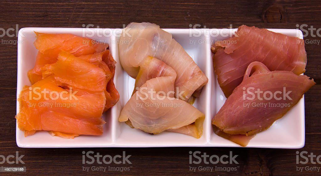 Trio of smoked fish on platter on wood from above stock photo