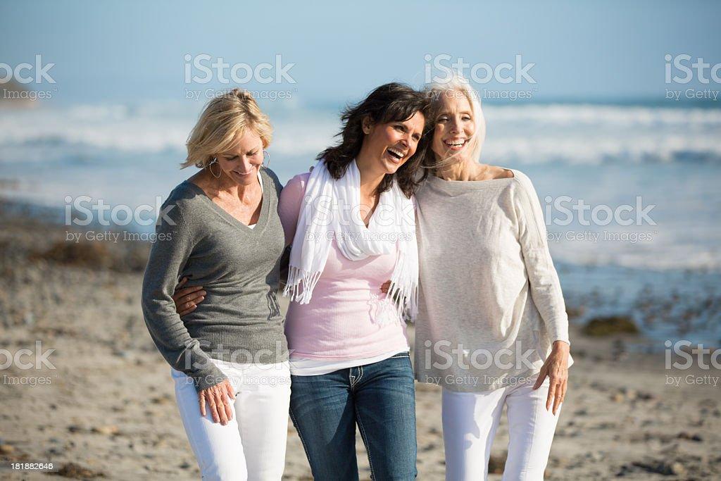 Trio of women walking at the beach stock photo