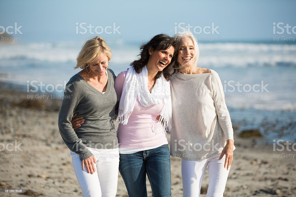 Trio of women walking at the beach stock photo