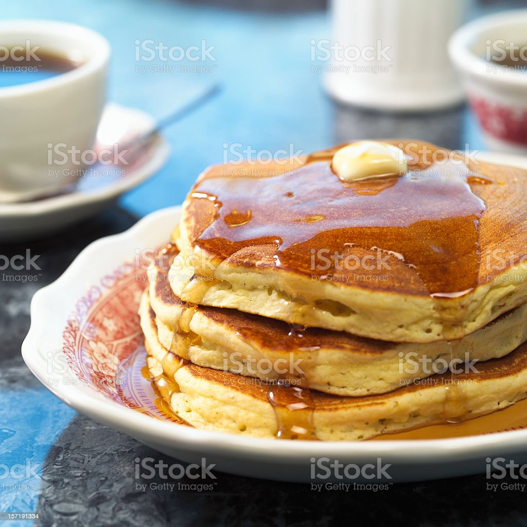Triple stack of pancakes and maple syrup and coffee stock photo