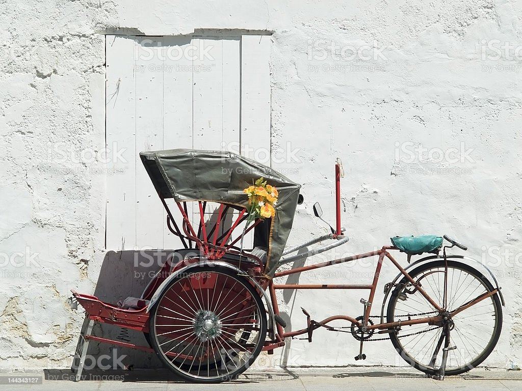 Trishaw parked at a white wall stock photo