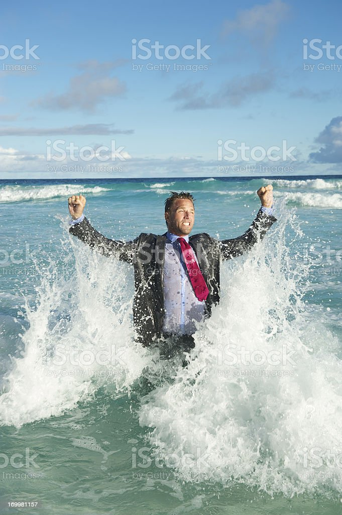 Triumphant Businessman Raises His Fists in Rough Waters royalty-free stock photo