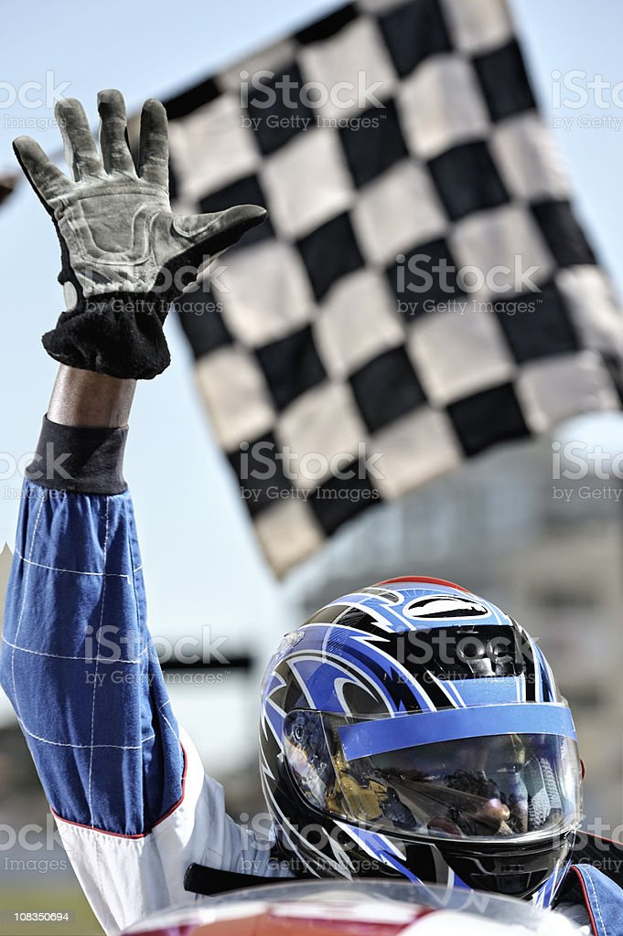 Triumphant racing driver waves at crowd stock photo